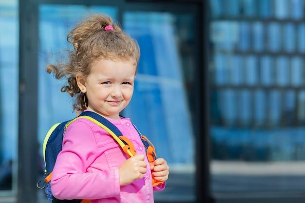 Маленькая милая девочка идет в первый класс. счастливый ребенок вернулся в школу. ребенок с портфелем в кампусе.