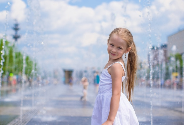 Little cute girl have fun in open street fountain at hot summer day