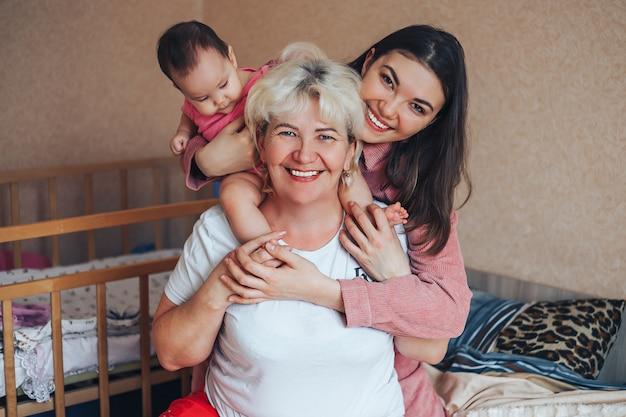 작은 귀여운 소녀, 그녀의 매력적인 젊은 어머니와 매력적인 할머니는 집에서 함께 시간을 보내고 있습니다.