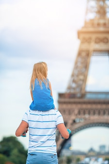Little cute girl and her father in paris near eiffel tower during summer french vacation