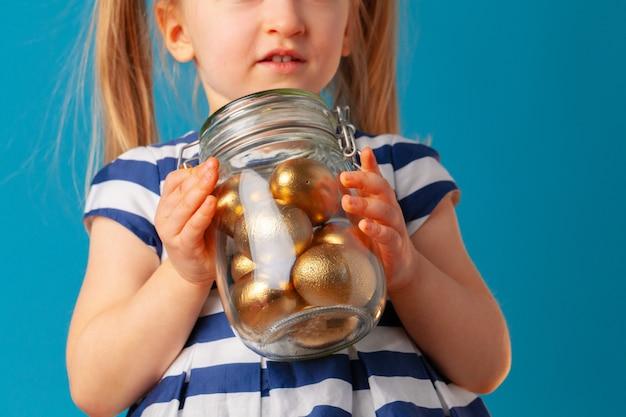 イースターのために着色された黄金の卵が付いているガラス瓶を保持しているかわいい女の子
