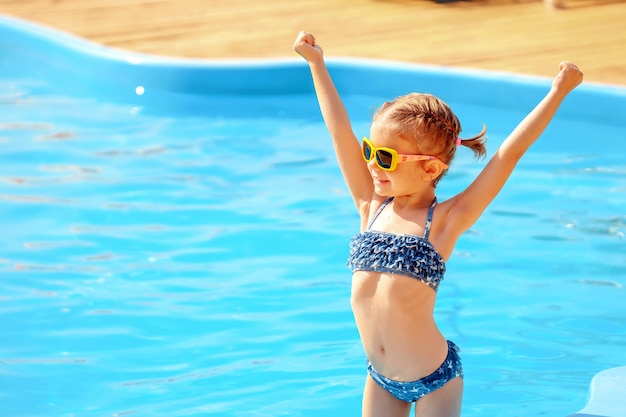 Little cute girl holding hands up near a swimming pool