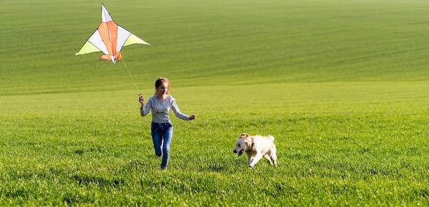 Маленькая милая девочка держит воздушного змея и бежит по полю зеленой травы с собакой