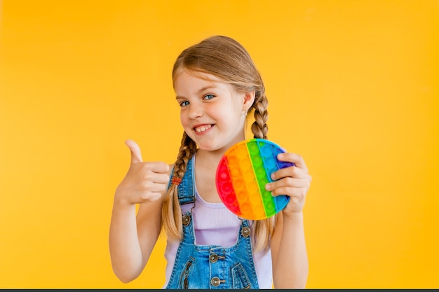 Little cute girl holding pop it antistress toy on yellow background, isolate. copyspace