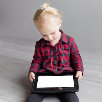 Little cute girl holding a tablet and looking at him