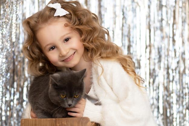 灰色の煙のような英国の猫を抱き締める小さなかわいい女の子