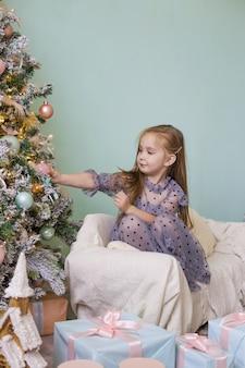 美しいドレスを着た小さなかわいい女の子がクリスマスツリーで遊んでいます。