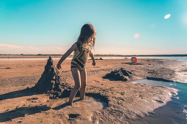 해변에서 모래를 가지고 노는 니트 수영복에 작은 귀여운 소녀.