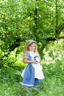 앨리스 의상에서 귀여운 소녀는 오래 된 골동품 시계를 보유하고있다.