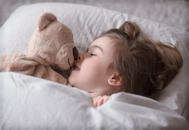 Маленькая милая девушка в постели с игрушкой
