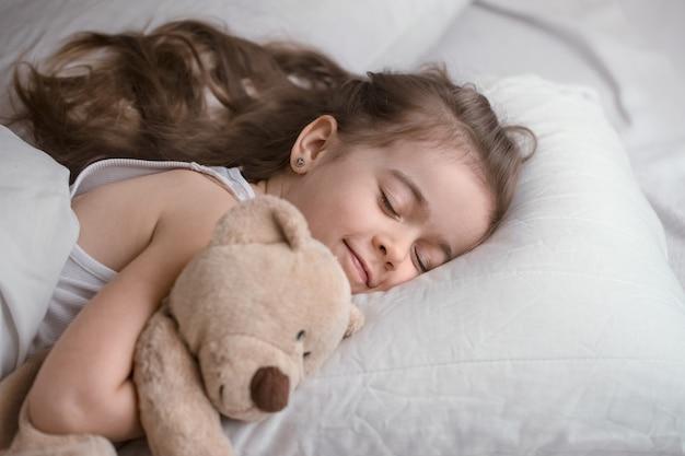 장난감 침대에서 귀여운 소녀