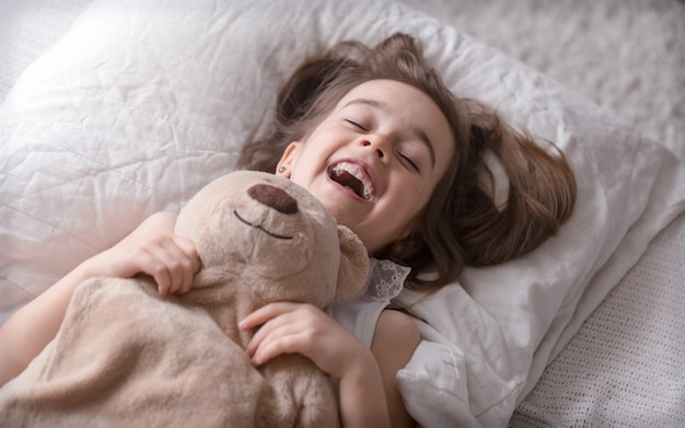Маленькая милая девочка в постели с игрушкой