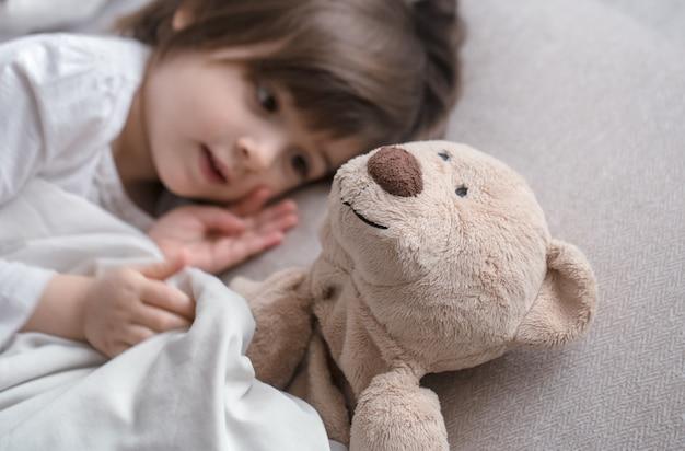 おもちゃとベッドでかわいい女の子