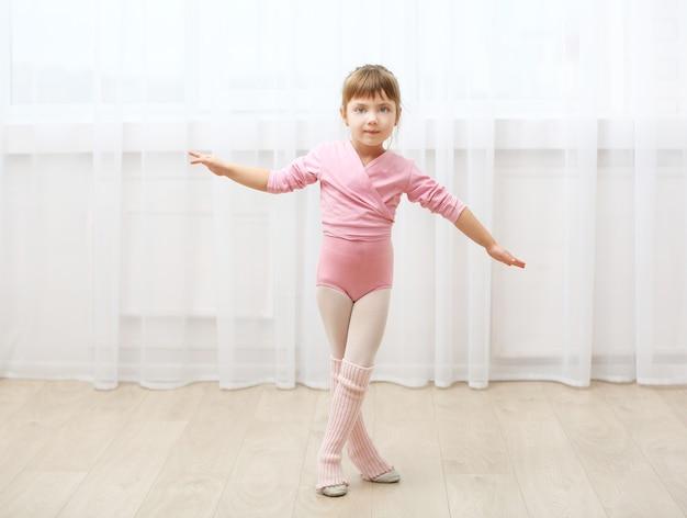 Маленькая милая девушка в розовом купальнике делает новое балетное движение в танцевальной студии