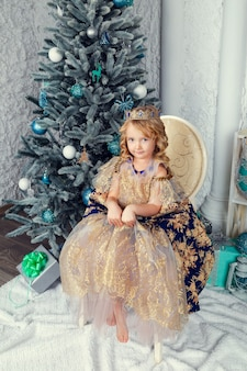 新年の木、美しいクリスマスの装飾の近くのプリンセスドレスのかわいい女の子
