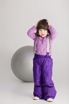 Маленькая милая девушка в фиолетовой одежде, держа его за голову и большой мяч для фитнеса на сером фоне.