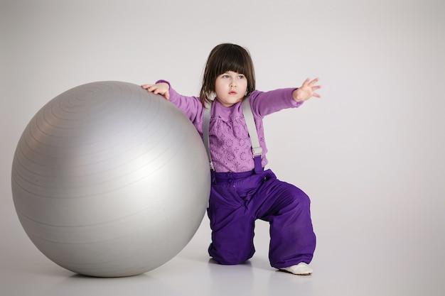 Маленькая милая девочка в фиолетовой одежде с большим мячом для фитнеса на сером фоне.