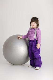 灰色の背景にフィットネスのための大きなボールと紫色の服を着た小さなかわいい女の子。
