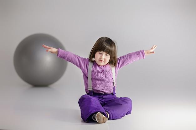 Маленькая милая девочка в фиолетовой одежде с раскинутыми руками и с большим мячом для фитнеса на сером фоне.