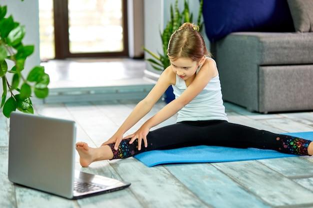 自宅で体操を練習して青いマットにスポーツウェアのかわいい女の子