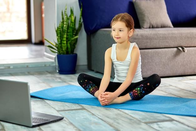 Маленькая милая девушка в спортивной одежде на голубой коврик практикующих гимнастику дома