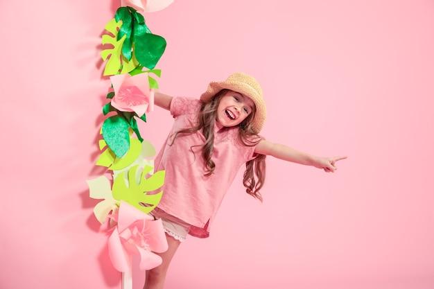 色の背景に夏の帽子の小さなかわいい女の子