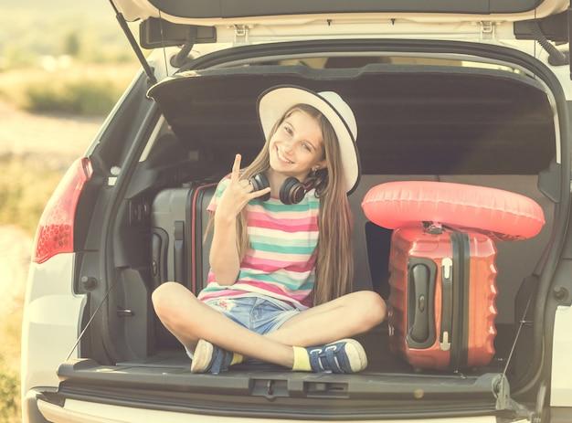 가방으로 자동차의 트렁크에 귀여운 소녀