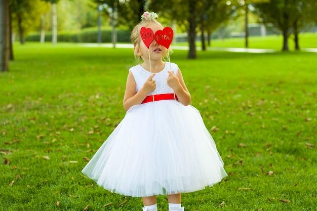 Маленькая милая девушка в белом платье в парке держит два сердца.