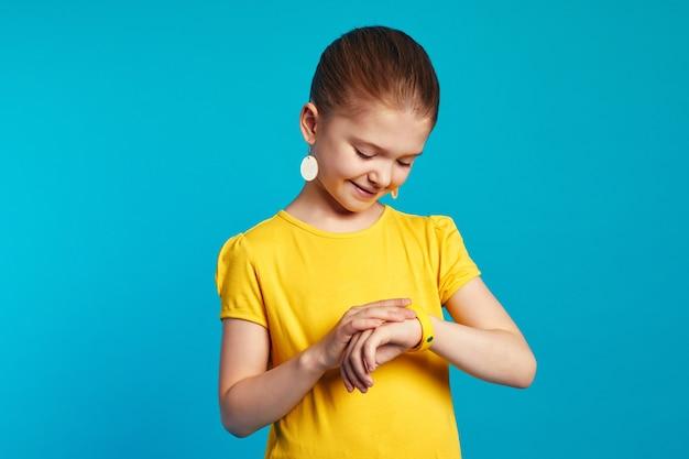 Маленькая милая девочка в желтой рубашке проверяет фитнес-браслет шагомер
