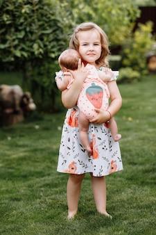 Маленькая милая девочка держит на руках новорожденную сестру и проводит с ней счастливое время на свежем воздухе
