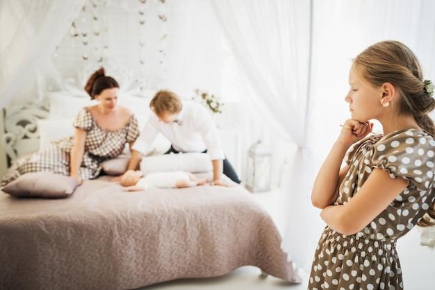 귀여운 소녀는 흐릿한 행복한 부모 옆에 침대에 누워 있는 갓난 남동생을 질투한다
