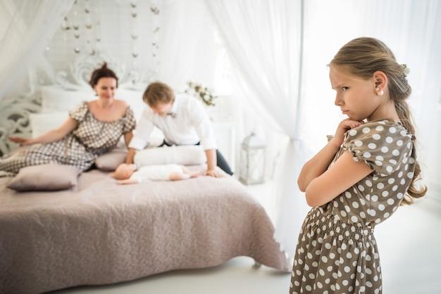 かわいい女の子はベッドに横たわっている彼女の生まれたばかりの兄弟に嫉妬しています