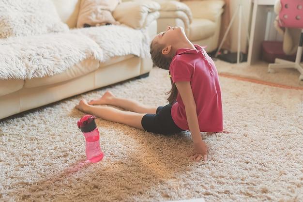 귀여운 소녀는 집에서 체조 연습