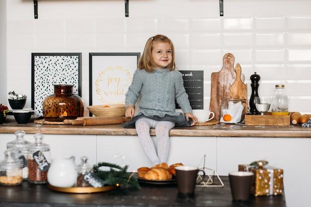 Little cute girl is sitting in kitchen.