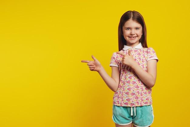 Маленькая милая девочка-ребенок показывает обоими указательными пальцами, показывая пустое пространство