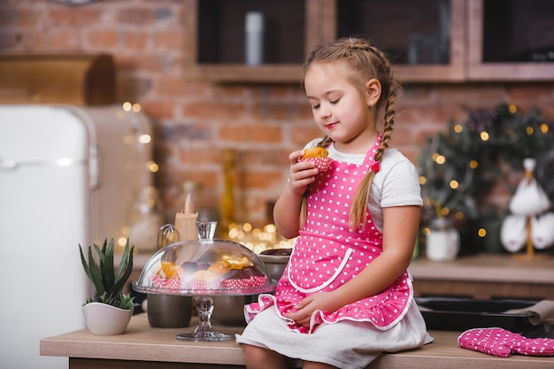 Little cute girl in the kitchen eating cupcakes
