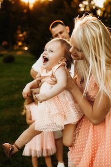 일몰에 대 한 그녀의 어머니의 팔에 비행하는 동안 웃 고 작은 귀여운 소녀. 젊은 아름 다운 여자를 공원에서 야외 그녀의 딸과 함께 연주.