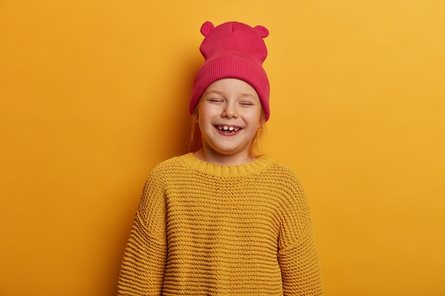 Little cute girl laughs happily, feels glad to receive new toy doll from parents, closes eyes, has fun indoor, wears hat with ears and loose knitted sweater, isolated over yellow wall.