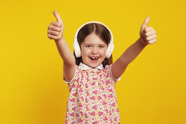Маленькая милая девушка слушает музыку в белых наушниках и показывает палец вверх