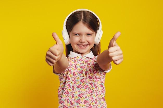 Маленькая милая девочка слушает музыку в белых наушниках и показывает палец вверх