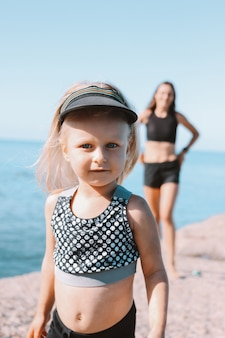 Little cute girl looking at camera on background of fit mom on beach