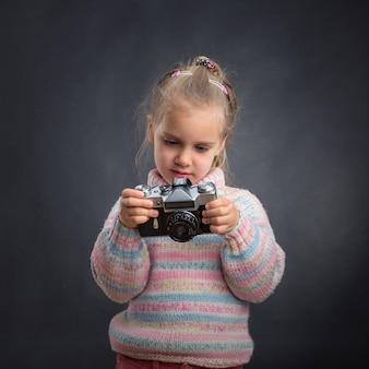 Маленькая милая девочка смотрит фотографии в камеру