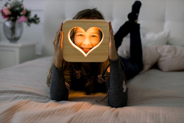 Little cute girl, lying on the bed at cozy home bedroom, and making different emotions, while holding wooden night lamp with heart cut out picture. wooden home decor.