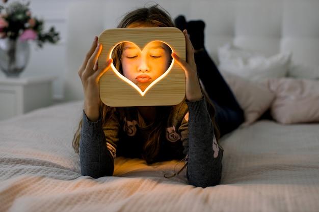 Маленькая милая девочка, лежа на кровати в уютной домашней спальне и производя разные эмоции, держа в руках деревянный ночник с вырезанным сердцем. деревянный домашний декор.