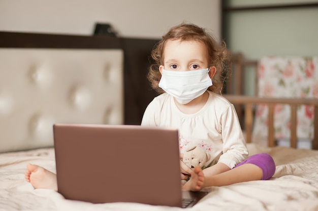 Little cute girl in a medical mask sitting on the bed and using a digital tablet laptop notebook. online call friends or parents.