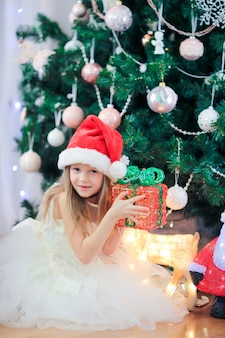 Little cute girl near christmas tree. children under christmas tree with gift boxes.