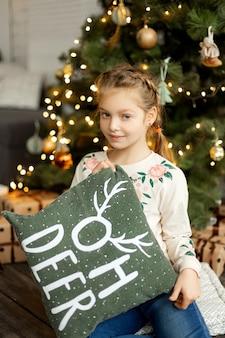 Маленькая милая девочка возле елки