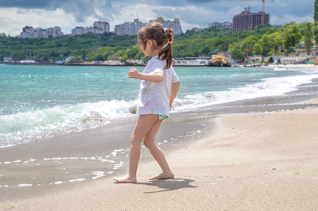 바다 해변에서 맑은 날에 작은 귀여운 소녀.