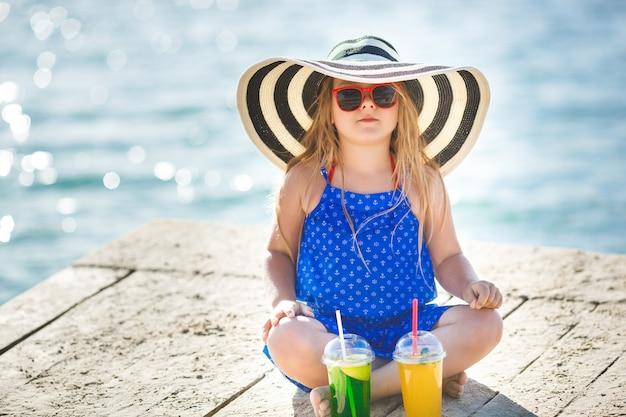 海の上のかわいい女の子。夏には帽子の少女。海岸線で愛らしい子。