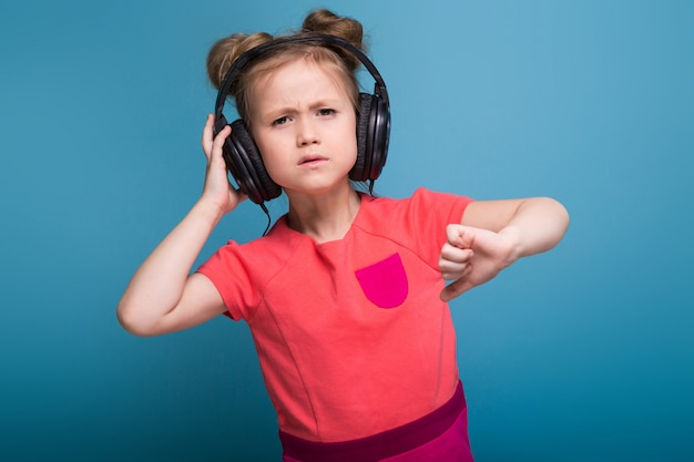 Little cute girl in pink dress and headphones